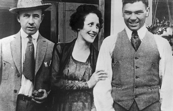 Left to right: Jack Kearns, manager of Jack Dempsey; Mrs. Maxine Dempsey; and Jack Dempsey, heavyweight champion. Mrs. Maxine Dempsey of Wells, Nevada, divorced wife of Jack Dempsey, has openly accused her former husband of evading military service during the war. In his draft questionnaire Dempsey claimed he was the sole supporter of his wife. This she denies and says she has letters from the heavyweight champion which will substantiate her charges. Mrs. Dempsey is now a dance hall girl in Wells, a small town near the Nevada Utah border. Department of Justice agents are investigating Mrs. Dempsey's charges.